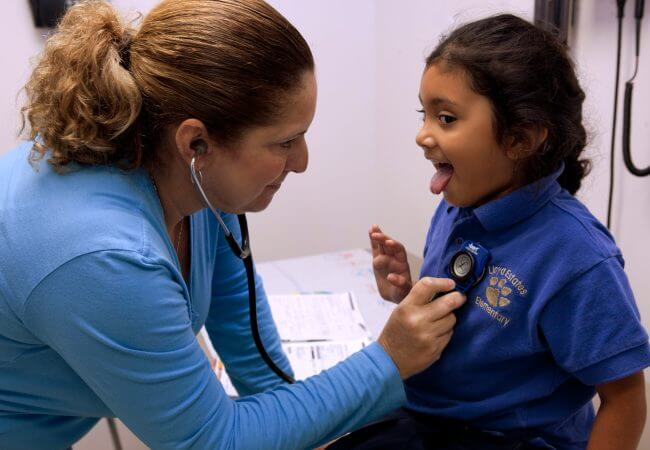 Nurse checks heartbeat of young patient, one of the many ways Nurses Affect Population's Health