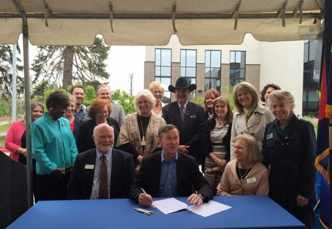 Gov. John Hickenlooper sits at a table surrounded by people as he signs legislation