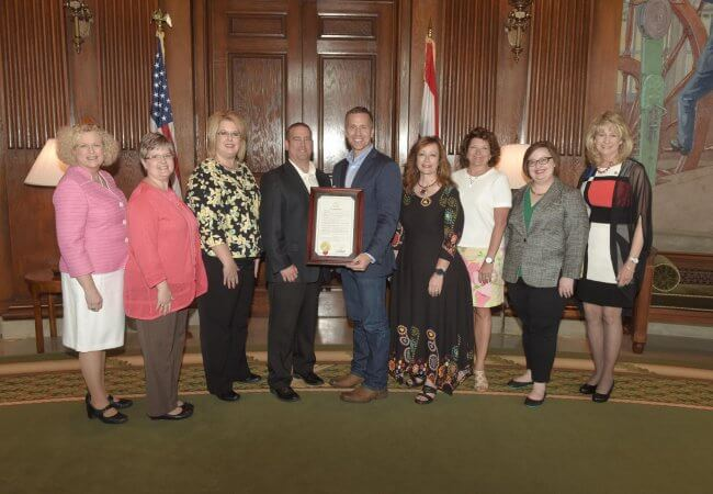 Missouri Governor Eric Greitens holds a proclamation for National Nurses Week surrounded by eight people