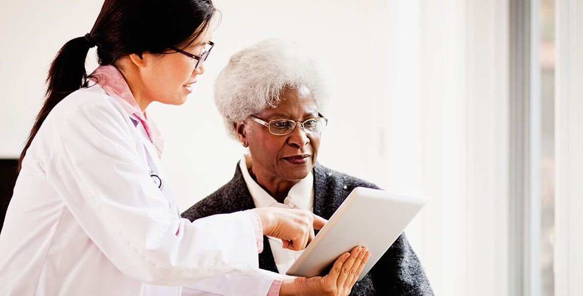 Nurse speaking to patient about her charts.