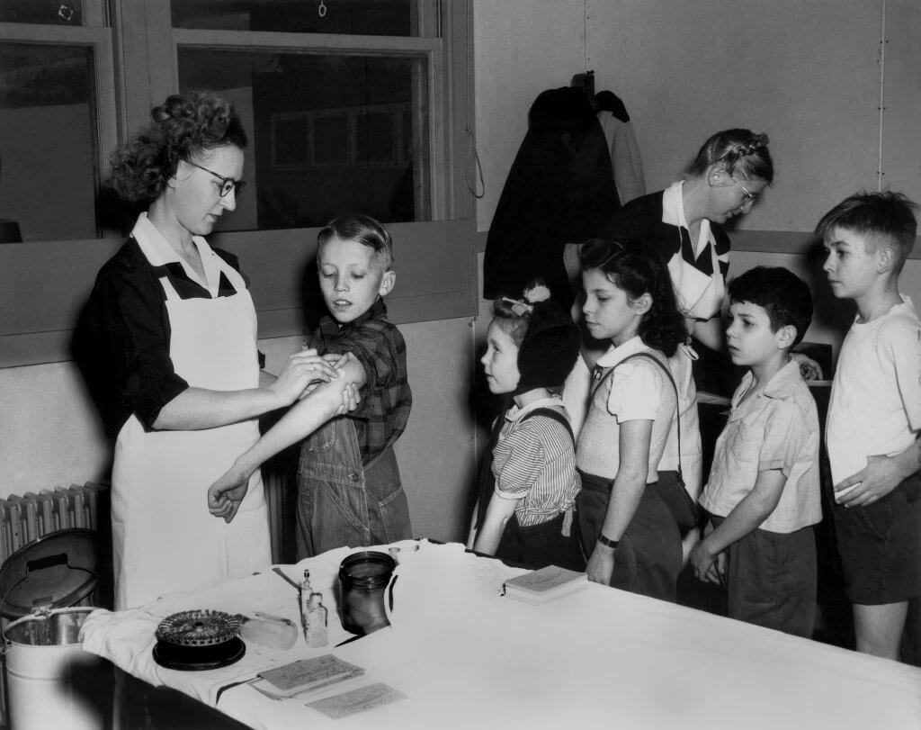 Public health nurse Gladys Johnson gives immunizations to children at Linden Elementary School in Oak Ridge, Tennessee in 1946.