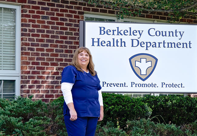 Angela Gray stands outside the Berkeley County Health department, but its sign.