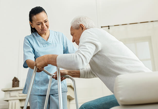 Nurse helping 50+ year old man with using a walker in a home setting