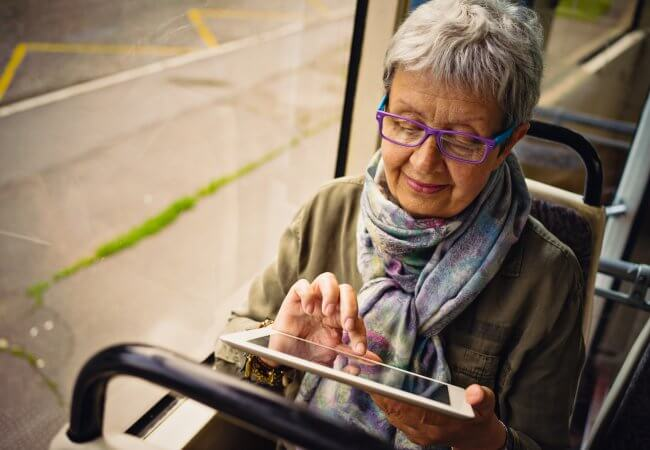 older women read the most-read Campaign for Action blog posts of 2019 using a tablet on a bus